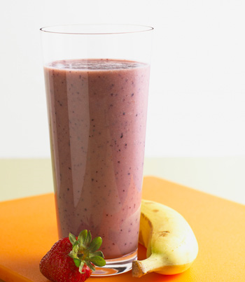 Tall glass with purple-ish colored smoothie  sitting on a table next to a banana and a strawberry.