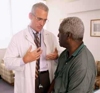 Doctor talking with older man in medical office
