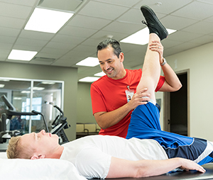 Physical therapist working with man on leg stretches.