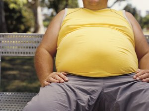 View of a man's belly as he sits on a park bench, wearing a yellow shirt